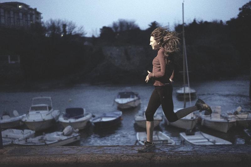 Junge Frau laeuft am Hafen entlang.