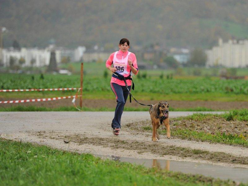 Laeuferin bei einem Laufwettkampf mit ihrem Hund an der Leine.