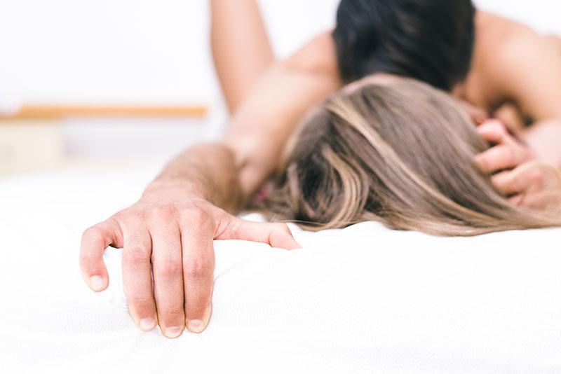 Bildausschnitt von einem Mann und einer Frau die nackt im Bett liegen.