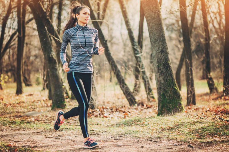 Young woman in sports wear running on the park lane
