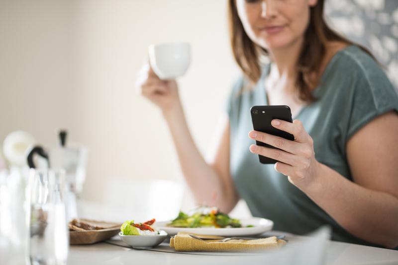 une femme tient son journal alimentaire sur son smartphone