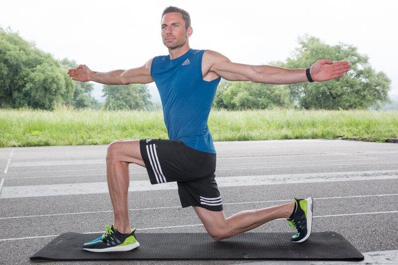 Jeune homme faisant une fente avant avec rotation du haut de son corps.
