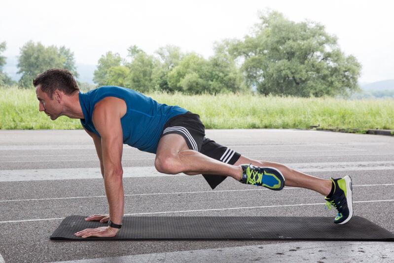 Jeune homme faisant une planche haute avec lever de genou.