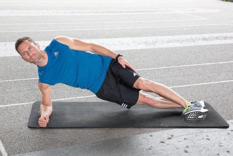 Jeune homme faisant une planche latérale basse avec lever de pied vers l'avant et vers l'arrière.