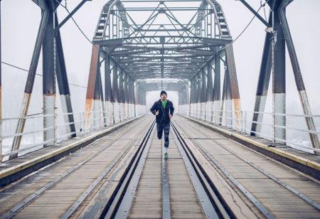 Ein Mann läuft auf einer Brücke im Nebel