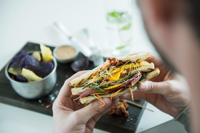 Ein Mann isst ein Sandwich