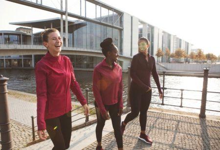 3 Frauen gehen nach ihrem Lauf am Wasser spazieren und haben Spaß