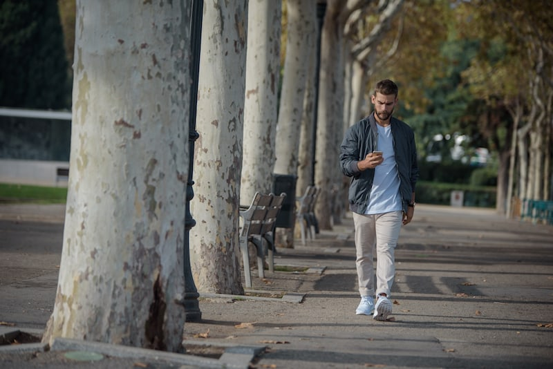 Young man walking and scrolling on his phone