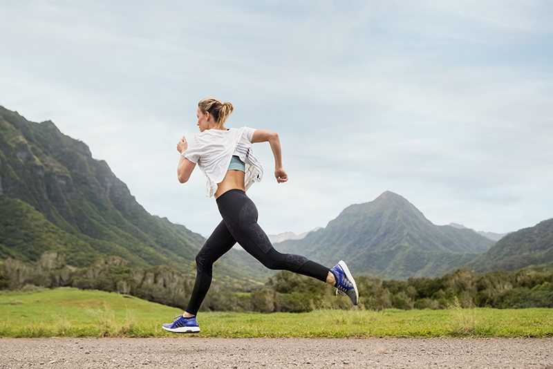 A woman running outside in adidas clothes