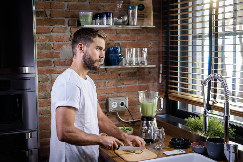 A man preparing a green smoothie in the kitchen