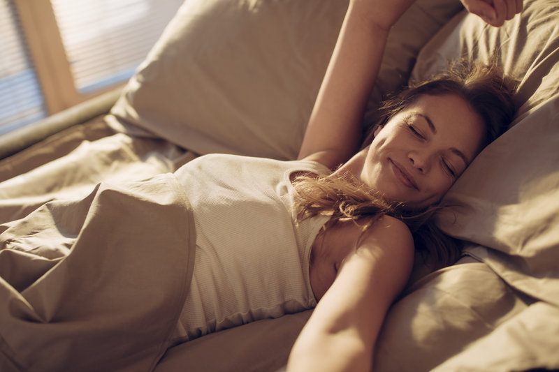Woman in bed is waking up