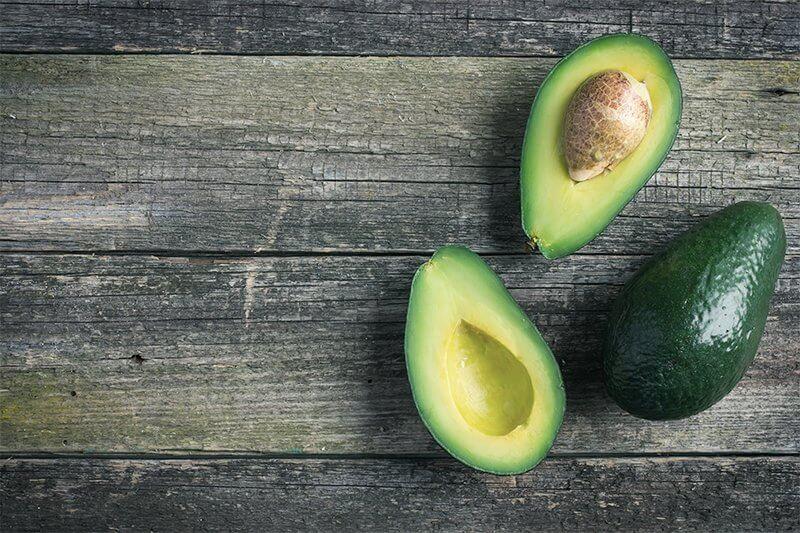 Foto von zwei Avocadohälften und einer Avocado