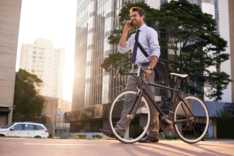 Shot of an attractive young man pushing his bicycle on the way to work