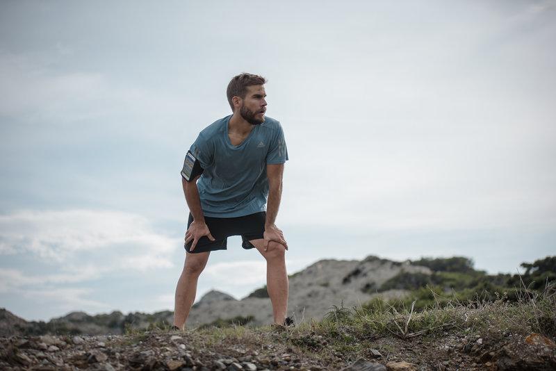 Ein Mann ist während dem Laufen außer Atem und muss eine Pause machen