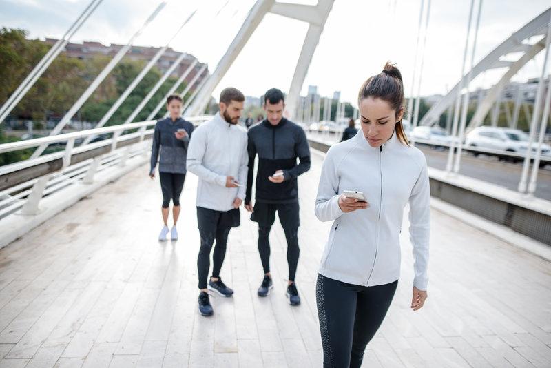 Zwei Frauen und zwei Männer schauen nach dem Lauf auf ihr Smartphone