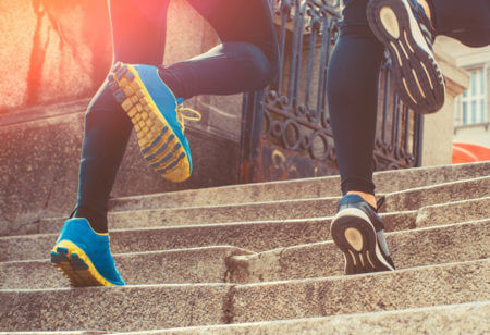 Close up of two runners running in their running shoes on the stairs