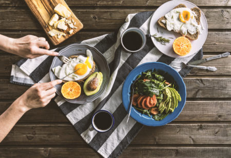 Top view shot of breakfast table. Poached egg with bread, sliced orange and avocado are on plates. Coffee mugs, cheese plate and salad with avocado, tomatoes and arugula are on the table with a grey tea towel. Hand slicing egg on the plate.