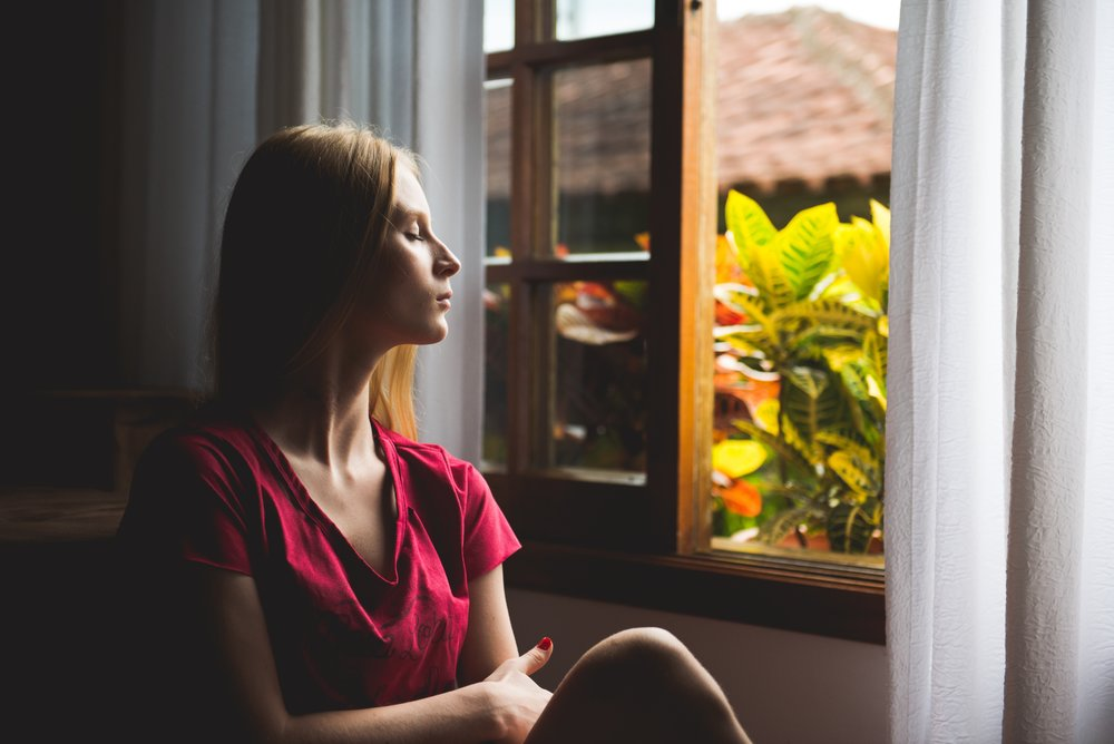 A woman sitting next to an open window with her eyes closed