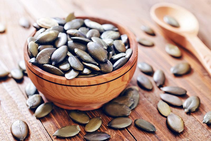 Pumpkin seeds in a wooden bowl.