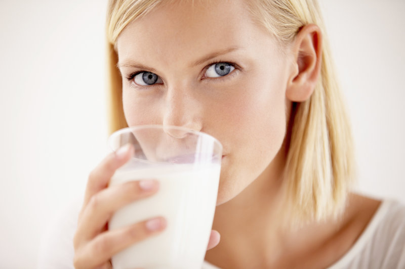 Pretty young woman sipping a glass of fresh milk