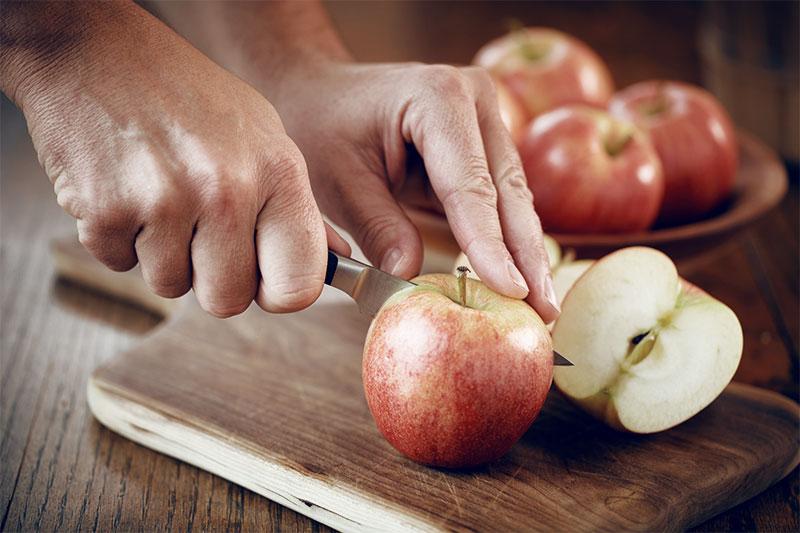 Jemand schneidet einen Apfel