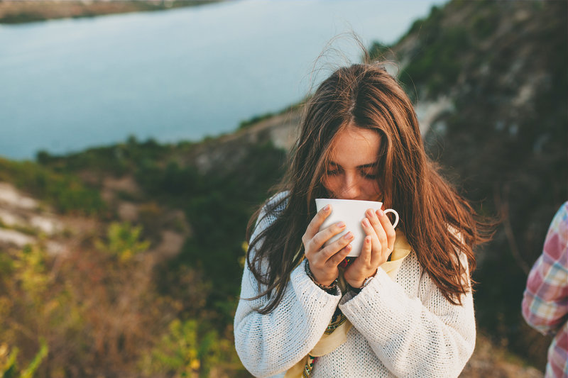 A young women drinking a cup of coffee outside