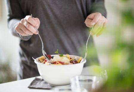 Man is preparing a big salad