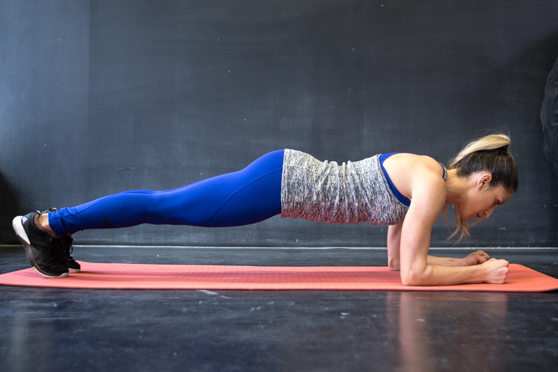 A woman is doing an ellbow push-up