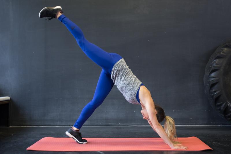 A woman is doing a single leg pike push-ups
