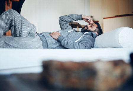 A man is lying in bed with headache