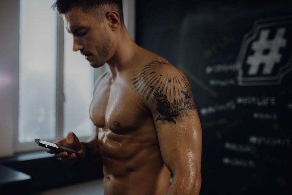 shirtless man looking at his phone