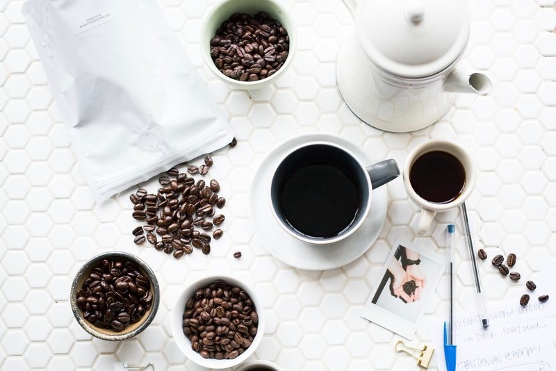 A mug of coffee and coffee beans on a table
