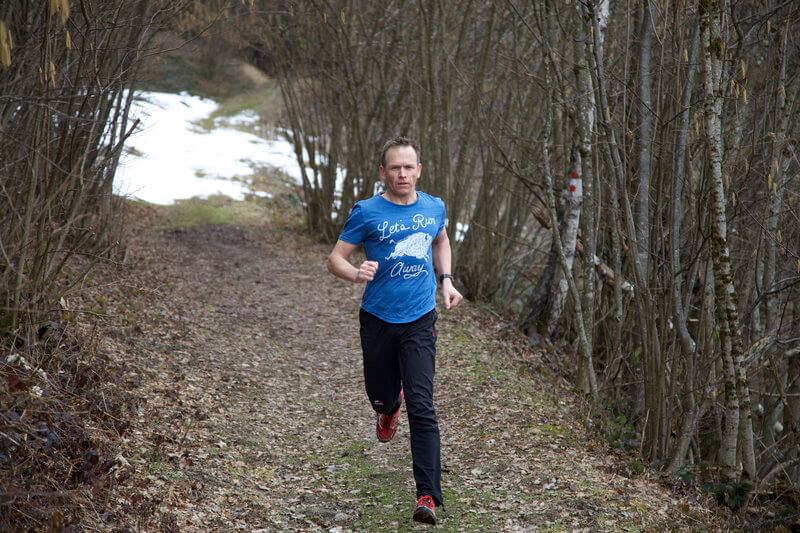 Man is running downhill in the forest.