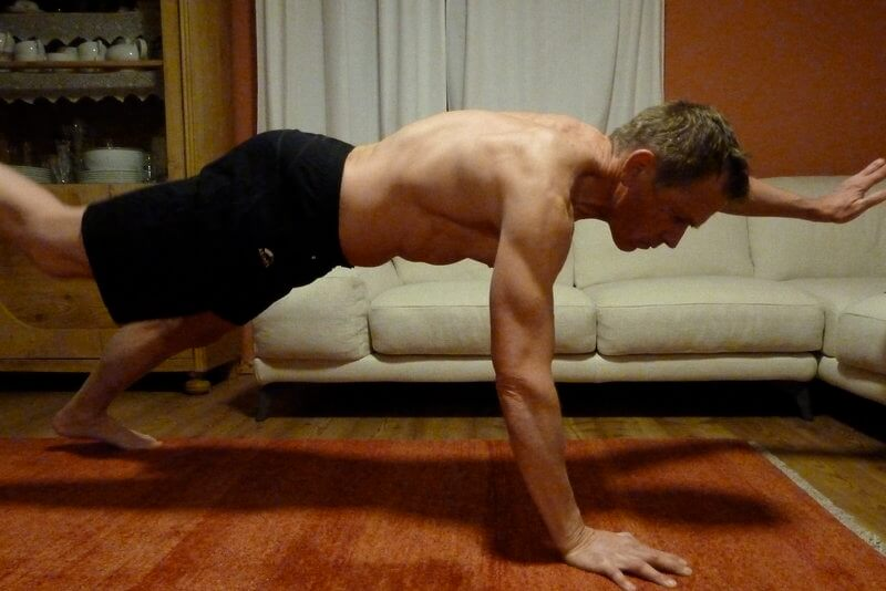 Athletic man doing bodyweight training in his livingroom.
