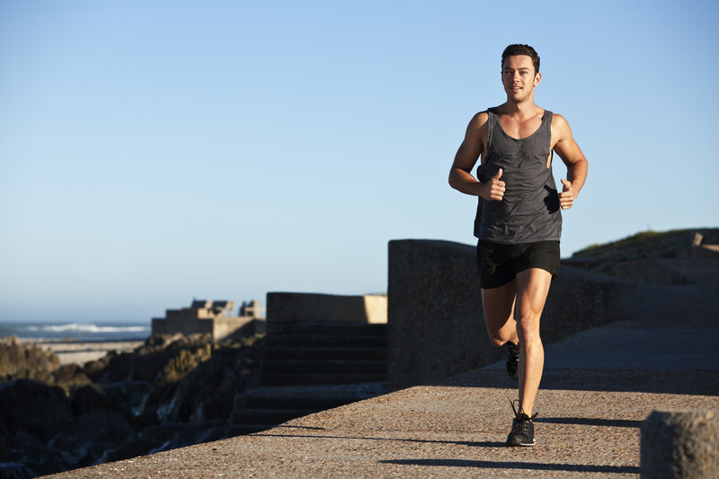 Muscular man jogging outdoors, seascape in background