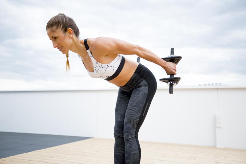 Woman is doing triceps kick backs
