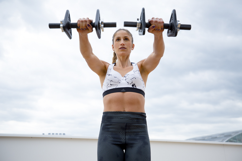 Women is doing front-to-side raises