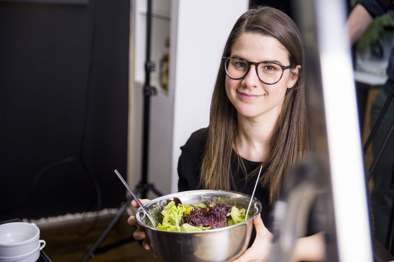 Young woman is holding a bowl of salad