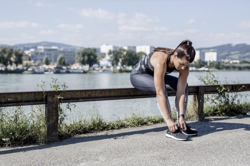 Young women ties her running shoes
