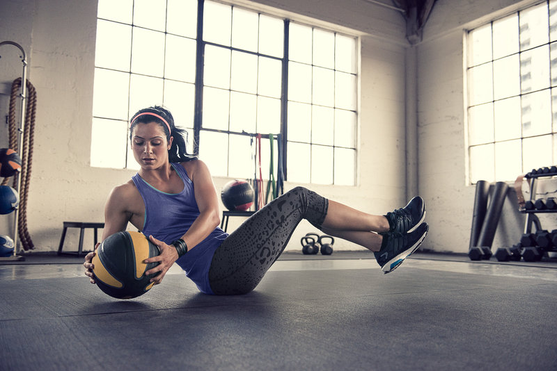 Woman is training in the gym with a medicine ball