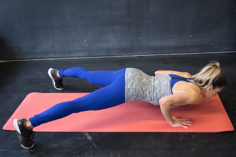A woman is doing push-up jacks