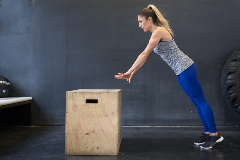 A woman doing a push-up on a box