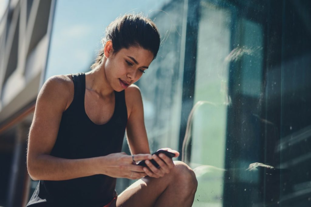 Woman looking at her phone to choose a workout