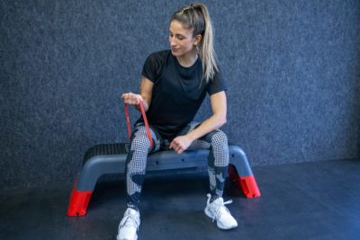 Woman doing bicep curls with resistance band