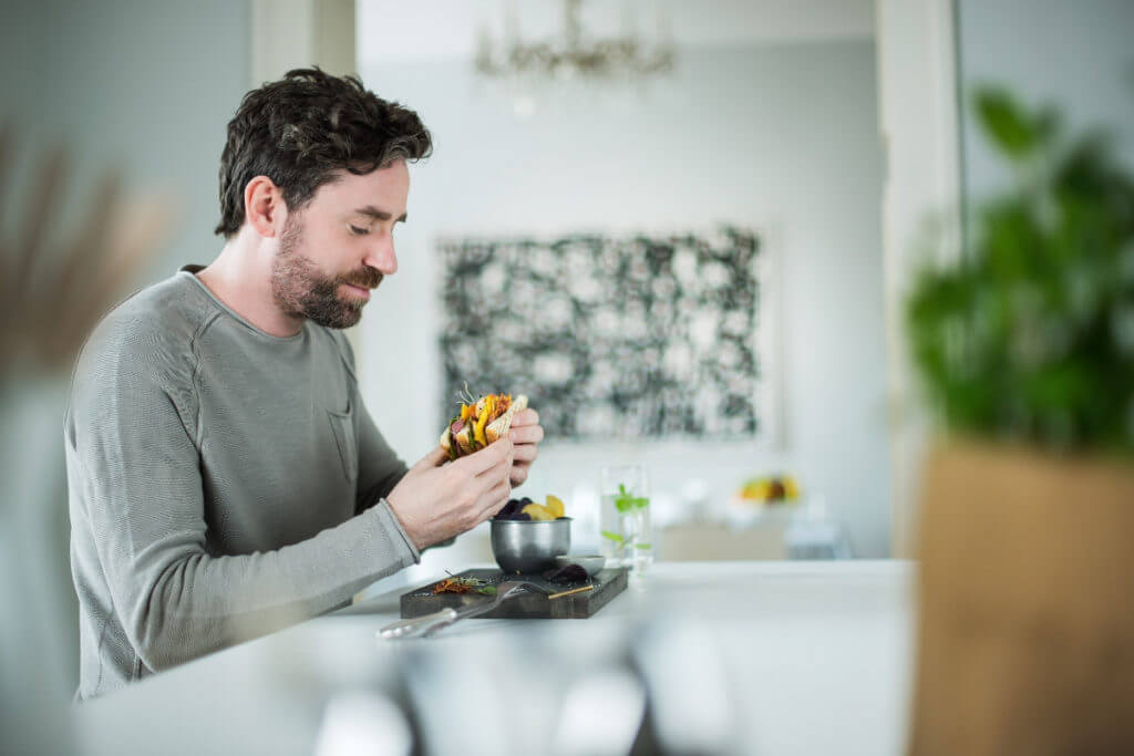man eating a sandwich by the table