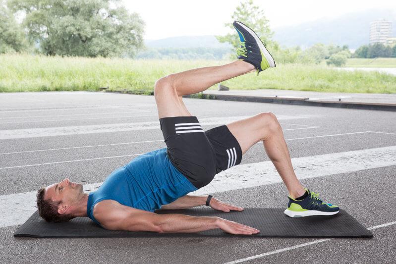 Homem fazendo uma ponte com elevação de perna.
