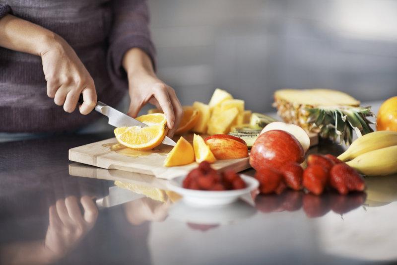 Junge Frau schneidet unterschiedliches Obst auf einem Holzbrett.