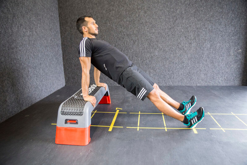 Young man is doing elevated dips.
