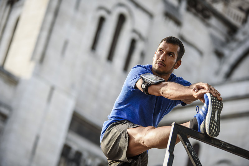 Athletic man stretching his leg after his running session.