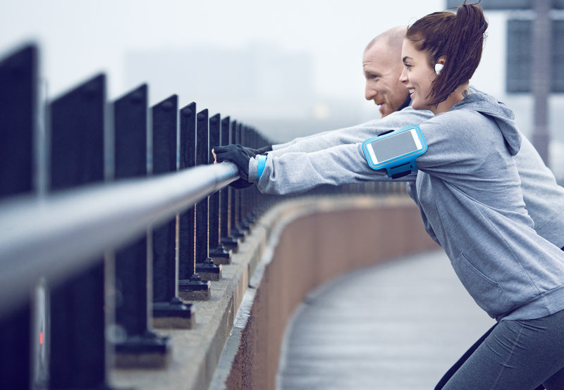 Female jogger and personal trainer stretching in the city